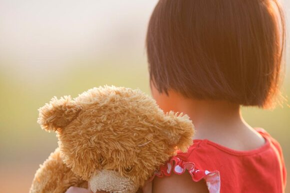 Looking at back of young girl with teddy bear