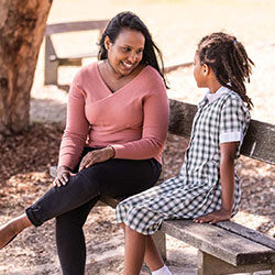 Woman speaking to girl student both sitting on bench