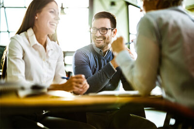 Happy couple talking to agent in meeting