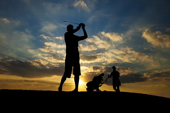 Two golfers silhouetted at sunset