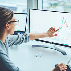 Business woman pointing at graph on screen